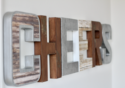 Cheers sign with rustic and industrial neutral letters.
