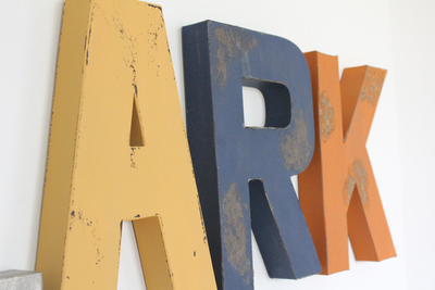 Camping themed nursery wall letters in yellow, orange, and navy colors.