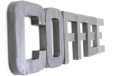"Silver ""metal"" letters spelling out Coffee with nail studs in the corners."