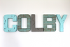 """wooden"" name wall letters spelling out COLBY in blue and grey."