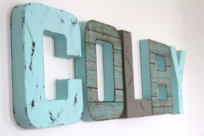 Boho boy nursery letters spelling out Colby in teal and aqua tones with a medium grey color mixed in.