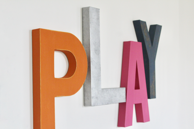 Colorful playroom play sign in different colors like orange, silver, blue, and pink.
