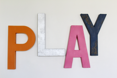 Playroom wall decor and play sign in orange, silver, pink, and navy.