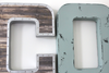 Kids name sign letters C and O in silver, brown, and blue.