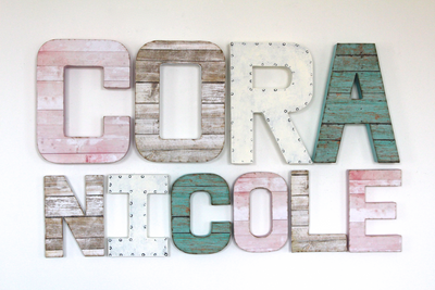 Girl's room name sign for Cora Nicole in shades of pink, white, and teal.
