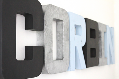 Modern nursery wall name letters in black, silver, and blue spelling out the name Corbin.