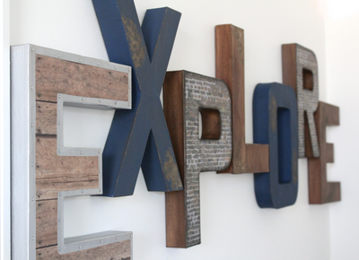 Rustic industrial farmhouse playroom wall sign spelling out the word Explore in different styles and colors.
