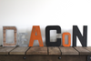 Industrial nursery wall letters spelling out Deacon in brown, silver, orange, and black letters.