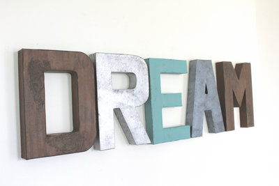 "Rustic playroom wall decor with the letters DREAM in different ""wooden"" colors such as brown, blue, and silver."