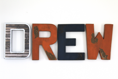 Boy room wall decor and customized wall letters spelling out the name Drew in silver, orange, and navy colors.