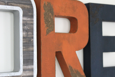 Distressed letters in orange and navy and an industrial letter with a nail trim design.