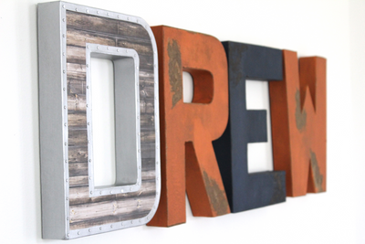 """Wooden"" and ""Metal"" orange and navy blue letters spelling out DREW."