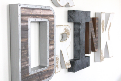 """Wooden"" and ""Metal"" wall letters spelling out the word Drink."