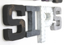 "Rustic ""wooden"" and ""metal"" letters spelling out the word SIPS in black, gray, white, and silver."
