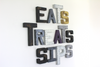 "Eclectic assortment of wall letters in different ""wooden"" and ""metal"" letters spelling out the words EATS SIPS and TREATS."