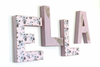 Pink room wall letters spelling out Ella with flowers.