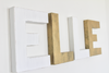 Girls modern wall letters spelling out the name ELLE in gold and white modern letters.