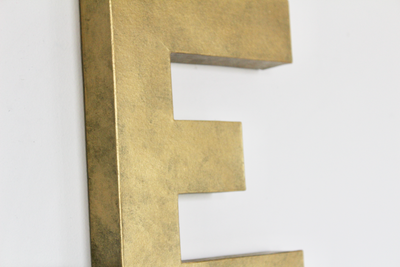 Modern gold wall nursery name letter E.