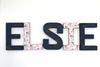 "Navy and Pink ""wooden"" girls boho nursery wall letters spelling out the name Elsie with flowers on the letters L and I."