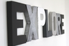 Monochrome Playroom Explore Sign Letters in black, white, silver, and gray.