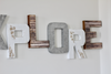 Playroom wall sign spelling out the word Explore in rustic and industrial letters.
