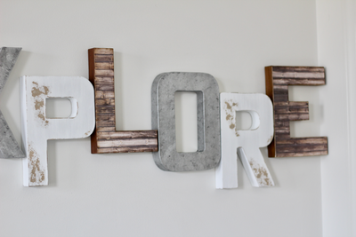 Playroom explore sign in browns, silvers, and white.