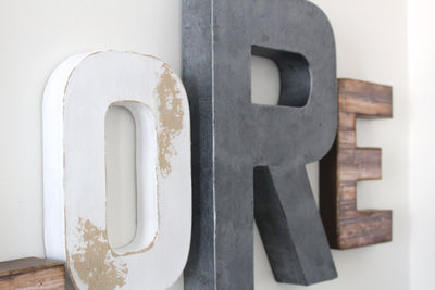 "White distressed ""wooden"" letter O and gray ""metal"" letter R."