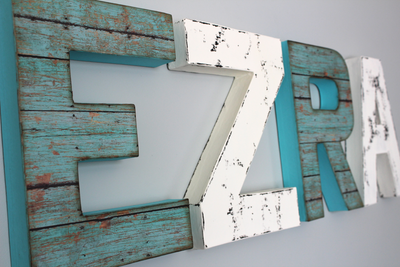Boho nursery name letters in teal and white colors spelling out Ezra.