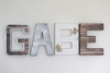 GABE name letters in an industrial finish in brown, silver, and white.