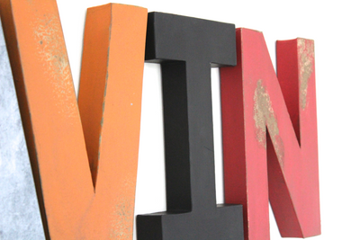Distressed letters in orange and red for kids bedroom wall decor.