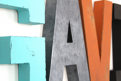 GAVIN custom wall letters for kids bedroom decor in different fun pops of colors featuring patina blue, gray, orange, black, and red.