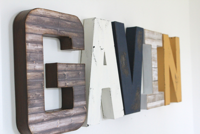 "Boy room name letters spelling out the name Gavin in natural ""wood"" tones with a pop of color with mustard orange letter N."