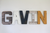 Gavin nursery letters in brown, white, navy, and mustard yellow.