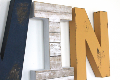 """wooden"" navy blue letter V and a beachy reclaimed ""wooden"" letter I with an orange letter distressed letter N."