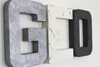 Monochrome nursery letters spelling out GEO in silver, white, and grey.