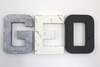 Monochrome nursery letters in silver, white, and grey spelling out GEO.