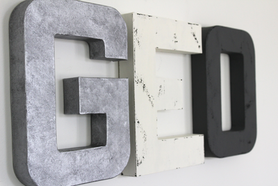 Monochromatic wall letters in silver, white, and gray spelling out GEO.