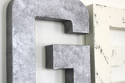 "Silver ""metal"" letter G and a white ""wooden"" letter E."