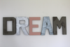 Playroom wall letters spelling out the word DREAM in silver, gray, and pink.