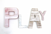 Play wall letter sign for a girls playroom in pink and white letters in different sizes and styles.