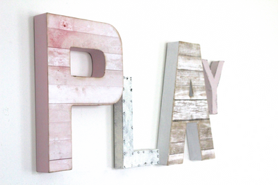 Girls pink playroom wall letters in different sizes spelling out the word PLAY.