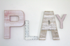 Girl's playroom wall decor play letters in pink and white.