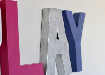 Play sign letters in pink, silver, and purple.