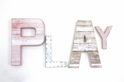 Play sign for girls playroom decor in different shades of pink and whites.