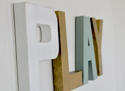 Modern play sign for children's wall decor in white, gold, and blue letters.
