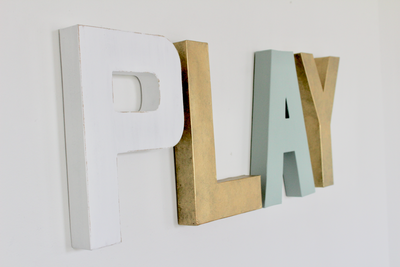 Play letters for playroom wall decor in gold, white, and soft blue wall letters.