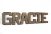 Bronze wall letters spelling out Gracie for industrial nursery decor.