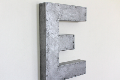 Silver galvanized letter E with a nail trim design going around the entire letter.