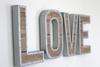 "Rustic ""wooden"" and ""metal"" love sign with a nailhead trim design."