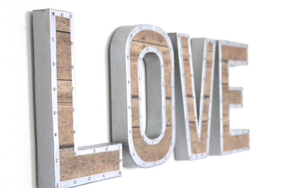 Rustic industrial wall letters spelling out the word LOVE.